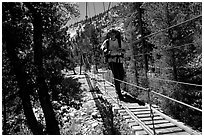 Crossing a river on a suspension footbridge. Kings Canyon National Park, California (black and white)