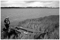 Canoeist deflating the canoe. Kobuk Valley National Park, Alaska (black and white)