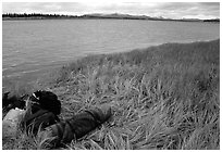 Gear and folded  canoe on a grassy riverbank of the Kobuk River. Kobuk Valley National Park, Alaska (black and white)