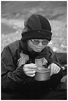 Backpacker eating camp food. Lake Clark National Park, Alaska (black and white)