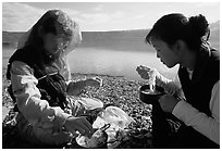 Backpackers eating noodles from a camp pot. Lake Clark National Park, Alaska (black and white)