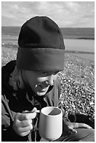 Backpacker drinking from a cup, with mosquitoes on her hat. Lake Clark National Park, Alaska (black and white)