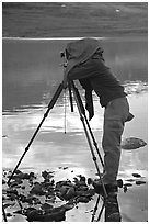 Large format photographer under dark cloth on the shores of Turquoise Lake. Lake Clark National Park, Alaska (black and white)