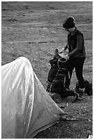 Backpacker unpacking backpack into the tent. Lake Clark National Park, Alaska (black and white)