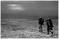 Two backpackers arrive at a ridge as a storm clears. Lake Clark National Park, Alaska (black and white)