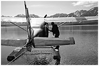 Pilot standing on floats of Floatplane, Twin Lakes. Lake Clark National Park, Alaska (black and white)