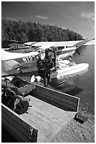 Backpackes being unloaded from floatplane in Port Alsworth. Lake Clark National Park, Alaska (black and white)
