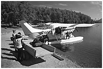 Backpackes being unloaded from floatplane to a trailer in Port Alsworth. Lake Clark National Park, Alaska (black and white)