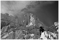 Looking up to woman scrambling on rocks on the East face of Mt Whitney. Sequoia National Park, California (black and white)
