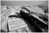 Hiker laying exhausted on Mt Whitney summit sign. Sequoia National Park, California (black and white)