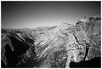 Hiker standing on top of Half-Dome, overlooking Tenaya Canyon. Yosemite National Park, California (black and white)