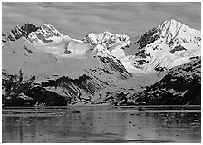 Coastal mountains with glacier dropping into icy fjord. Glacier Bay National Park, Alaska, USA. (black and white)