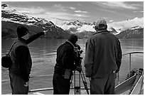Crew filming from the deck of a boat. Glacier Bay National Park, Alaska, USA. (black and white)