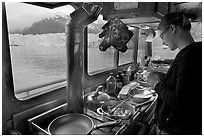 Woman preparing a breakfast aboard small tour boat. Glacier Bay National Park ( black and white)
