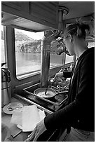 Woman cooking eggs aboard small tour boat, with glacier outside. Glacier Bay National Park ( black and white)