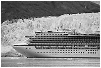 Cruise ship dwarfed by the face of Margerie Glacier. Glacier Bay National Park, Alaska, USA. (black and white)