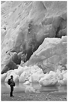 Hiker looking at ice wall at the terminus of Reid Glacier. Glacier Bay National Park, Alaska, USA. (black and white)
