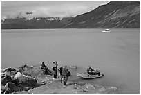Film crew met by a skiff after shore excursion. Glacier Bay National Park, Alaska, USA. (black and white)