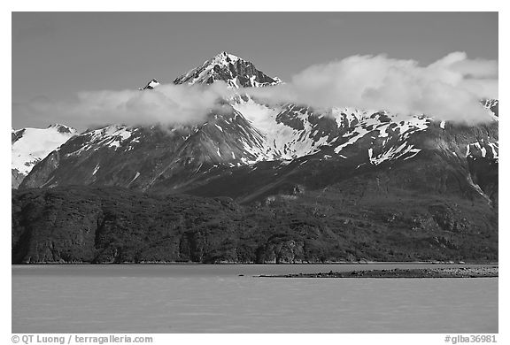Snowy peaks and clouds raising above turquoise waters in sunny weather. Glacier Bay National Park (black and white)