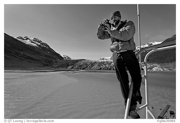Photographer perched on boat with Reid Glacier behind. Glacier Bay National Park (black and white)