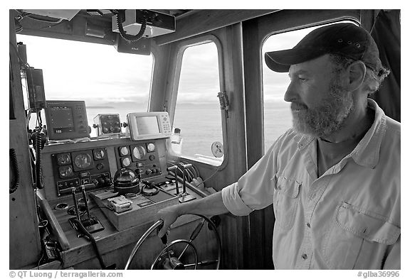 Captain steering boat with navigation instruments. Glacier Bay National Park (black and white)