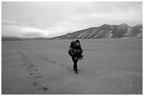 Backpacker hikes in sand-like ash, Valley of Ten Thousand smokes. Katmai National Park, Alaska (black and white)