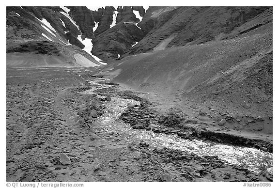 Stream flows from verdant hills into  barren valley floor. Katmai National Park (black and white)