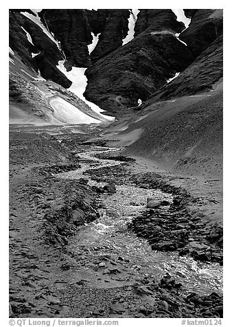 Stream flows from the verdant hills into the barren floor of the Valley of Ten Thousand smokes. Katmai National Park (black and white)
