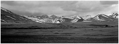 Desert-like ash-covered valley surrounded by snowy peaks. Katmai National Park (Panoramic black and white)