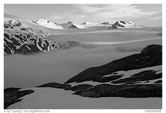 Low clouds, partly melted snow cover, and mountains. Kenai Fjords National Park (black and white)