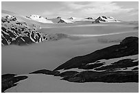 Low clouds, partly melted snow cover, and mountains. Kenai Fjords National Park ( black and white)