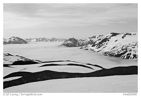 Dark bands of freshly uncovered terrain, snow, and low clouds, dusk. Kenai Fjords National Park, Alaska, USA.