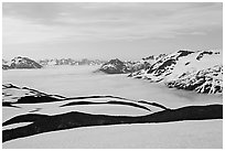 Dark bands of freshly uncovered terrain, snow, and low clouds, dusk. Kenai Fjords National Park, Alaska, USA. (black and white)