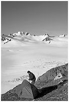 Camper exiting tent above the Harding ice field. Kenai Fjords National Park, Alaska, USA. (black and white)