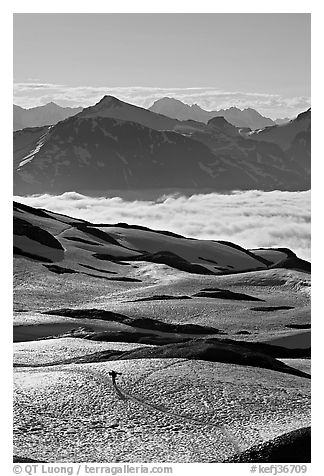 Mountains and sea of clouds, hiker on snow-covered trail. Kenai Fjords National Park (black and white)