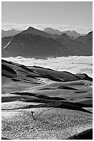 Mountains and sea of clouds, hiker on snow-covered trail. Kenai Fjords National Park, Alaska, USA. (black and white)