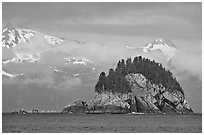 Rocky islet and snowy peaks, Aialik Bay. Kenai Fjords National Park, Alaska, USA. (black and white)