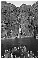 Passengers looking at waterfalls from  bow of tour boat, Cataract Cove. Kenai Fjords National Park ( black and white)