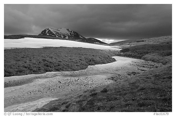 Snow nevesand mountains under dark storm clouds. Lake Clark National Park (black and white)