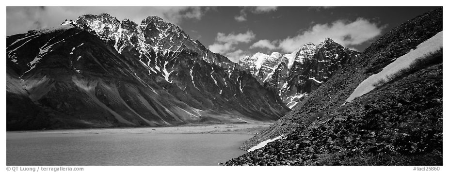 Rugged mountains rising above lake with turquoise waters. Lake Clark National Park (black and white)