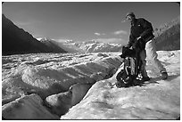 Hiker reaching into backpack on Root glacier. Wrangell-St Elias National Park ( black and white)