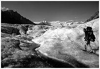 Backpacker with large pack on Root glacier. Wrangell-St Elias National Park ( black and white)