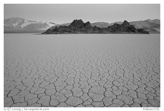 Tiles in cracked mud and Grand Stand, Racetrack playa, dusk. Death Valley National Park (black and white)