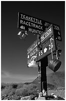 Tea kettle Junction sign, adorned with tea kettles. Death Valley National Park ( black and white)