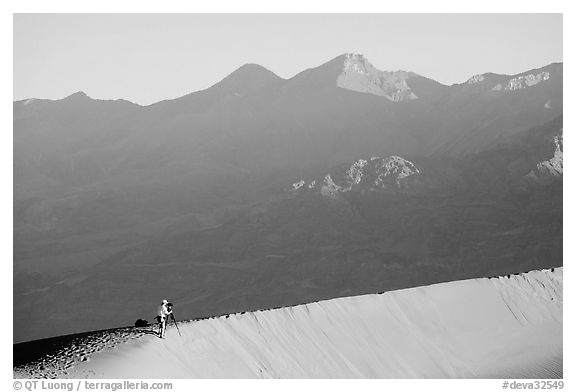 Photographer on dune ridge at sunrise. Death Valley National Park (black and white)