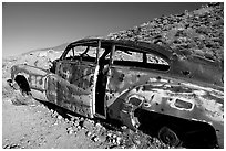 Car with bullet holes near Aguereberry camp, afternoon. Death Valley National Park, California, USA. (black and white)