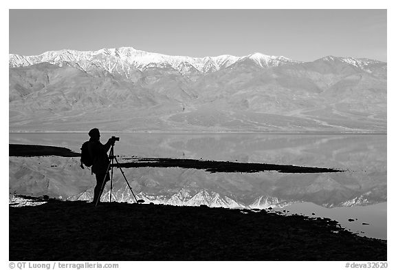 Photographer and Panamint range reflected in a seasonal lake, early morning. Death Valley National Park (black and white)