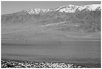 Kayakers in ephemeral Manly lake, and Panamint Range. Death Valley National Park, California, USA. (black and white)