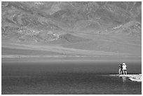 Two tourists on shore of rare lake on the floor of the Valley. Death Valley National Park ( black and white)