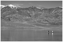 Tourists wading in the rare seasonal lake. Death Valley National Park, California, USA. (black and white)